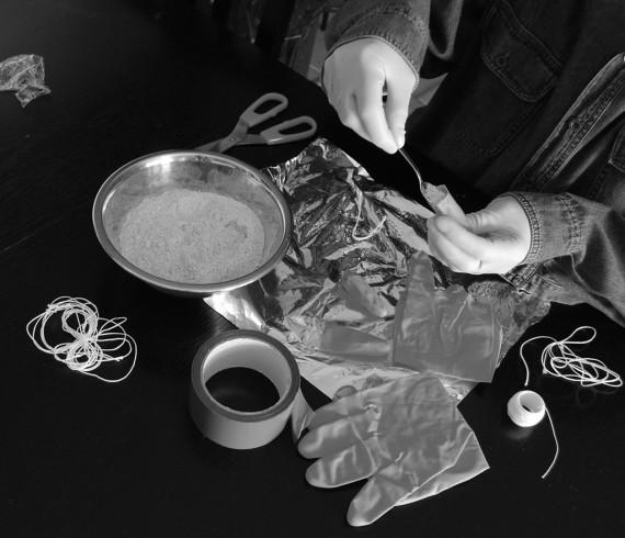 Krokett nagyságú kapszulák készülnek a gumikesztyű levágott ujjaiból.